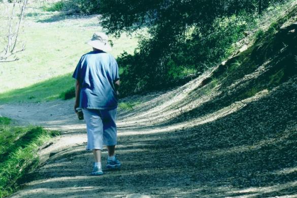 persona con sombrero caminando en un sendero practicando ejercicio aerobico facil y efectivo