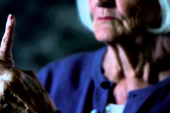 mujer adulta mayor de cabello blanco mirando y tomando su mano derecha con la izquierda