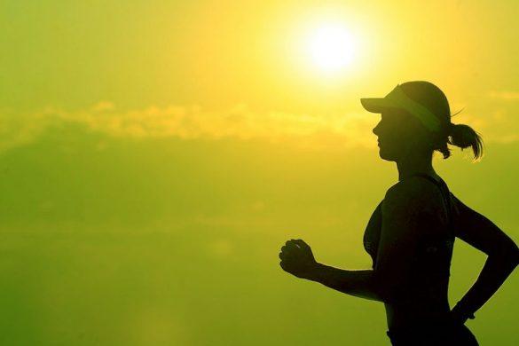 silueta de una mujer con gorra corriendo en el atardecer haciendo una rutina cardiovascular