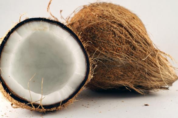 coco entero y una mitad de coco conoce los beneficios del agua de coco
