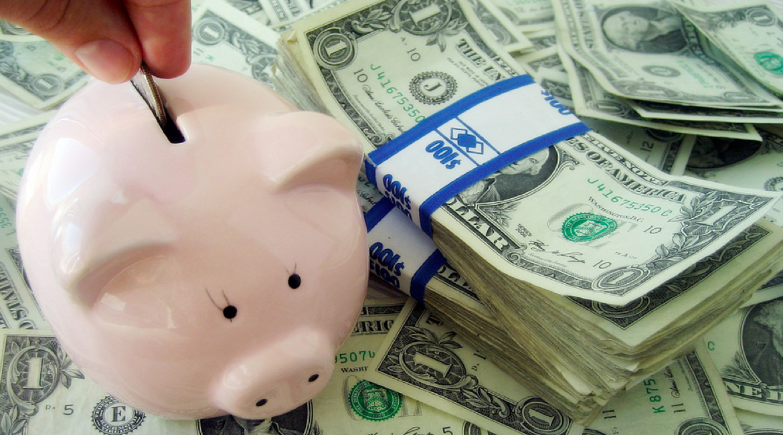 cientos de dolares en fajos una mano depositando una moneda en alcancia de cerdo