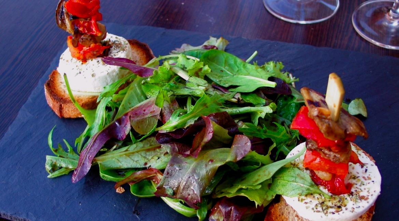 mesa mantel negro par de panes con queso en brocheta y ensalada nutritiva de berros