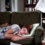 mujer de cabello pelirrojo durmiendo en un sofa color cafe sobre su lado izquierdo