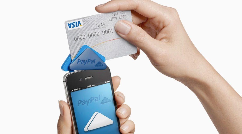 manos de mujer con celular pasando un tarjeta de credito por una terminal de compra en linea