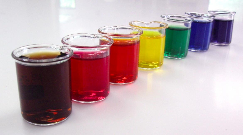 siete vasos de vidrio con sustancia de diferentes colores como roja cafe amarilla azul verde