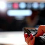 fotografia de television y mano de mujer con unas pintadas sosteniendo un control remoto