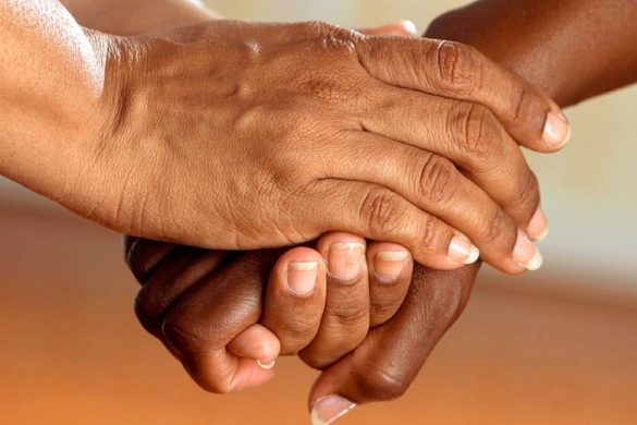 un par de manos morenas entrelazadas simbolizando que entre mas amigos igual a menos dolor