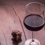 pedazo de chocolate sobre mesa de madera y copa de vino tinto alimentos que calman el estres