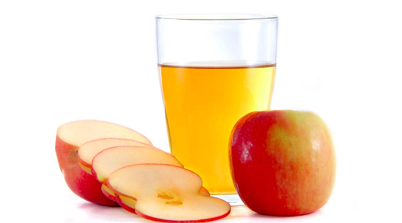 manzana roja en rodajas una manzana entera y vaso de vidrio con vinagre de manzana