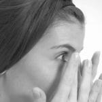 fotografia en blanco y negro de mujer de cabello largo con sus manos sobre sus ojos