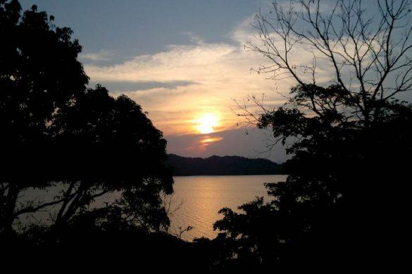 puesta del sol en catemaco llamada la tierra de los brujos con mar y arboles a la vista