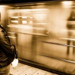 mujer de chamarra negra viendo pasar el metro y su reflejo en el vagon
