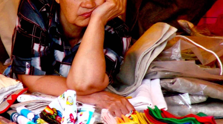 mujer recargada en su brazo sobre telas ejemplificando el dia mas aburrido del siglo xx