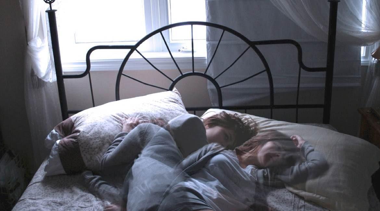 mujer acostada en su cama con ventana abierta sin poder dormir como eliminar el insomnio
