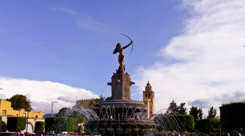 foto de monumento de mujer con arco edificios y el cielo ixmiquilpan un lugar para visitar