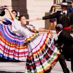 grupo de personas con trajes tipicos de jalisco bailando el jarabe tapatio en una plaza
