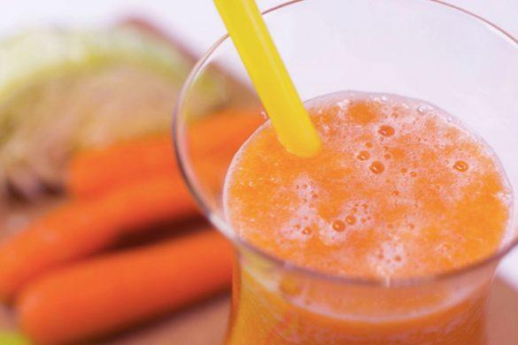 vaso de vidrio con jugo de zanahoria popote amarillo y al fondo dos zanahorias sobre mesa