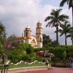 palmeras plantas bancas faros de luz mujer caminado y al fondo iglesia en color blanco