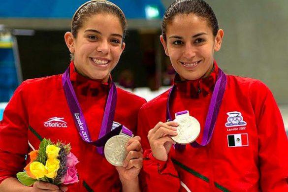 pareja de mujeres mexicanas deportistas luciendo sus medalla de plata en uniforme rojo