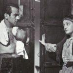 fotografia de un boxeador con guantes de box y toalla junto a una mujer y una puerta