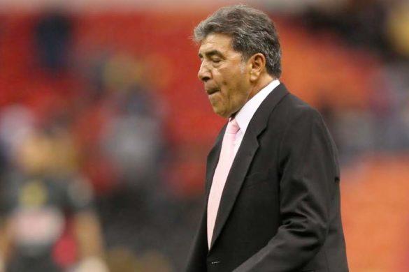 fotografia en estadio del ex futbolista carlos reynoso de traje negro y corbata rosa