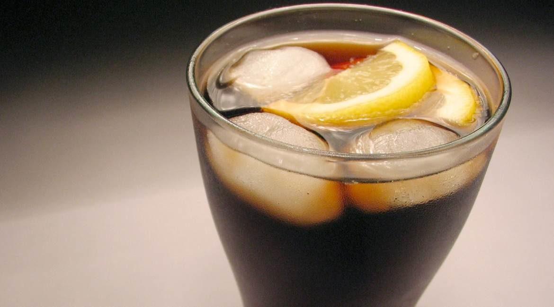 vaso de vidrio con refresco de cola hielo y rodaja de limon en una superficie blanca
