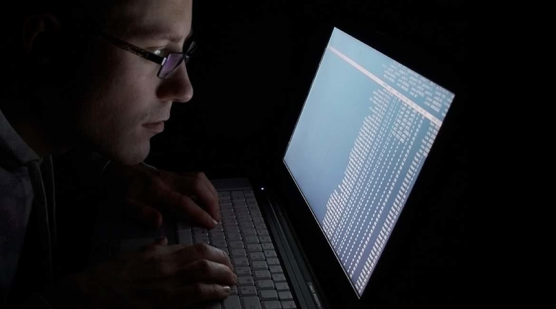 hombre con lentes frente a su laptop con pantalla encendida en habitacion totalmente oscura