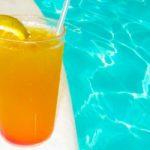 alberca con agua y un vaso de jugo de naranja con rodaja y popote de plastico