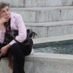 mujer de lentes sentada junto una fuente de pantalon negro saco rosa y manos sobre su boca
