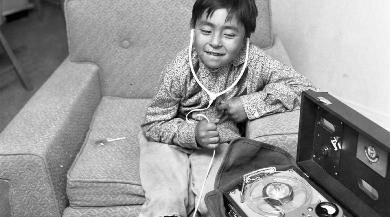 fotografia de nino en sentado en sillon escuchando musica desde unos audifonos