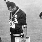 podio de las olimpiadas con tres deportistas dos de ellos hombres de color con el puno arriba