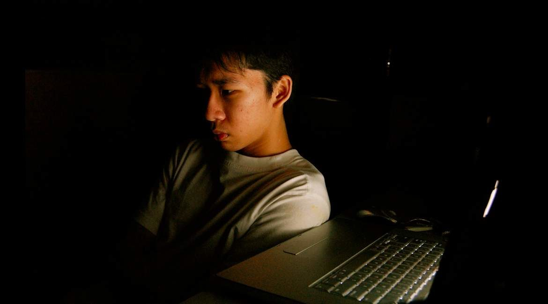 hombre a media luz frente una computadora descubre como reducir el cortisol en el cuerpo