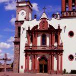 fotografia de una iglesia de amealco con pared blanca columnas puerta roja y campanas