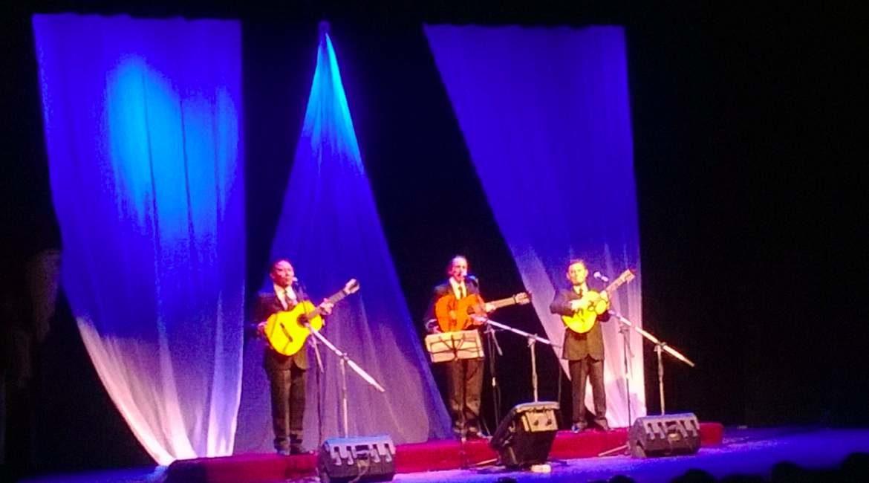 escenario con cortinas luces y tres hombres de traje tocando la guitarra cantando boleros