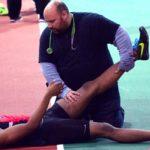 atleta en suelo con calambre y doctor estirando su pierna sabes que provoca los calambres