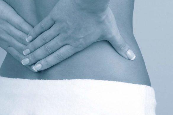 mujer con las manos en la espalda y toalla blanca conoce la causa del dolor de espalda baja