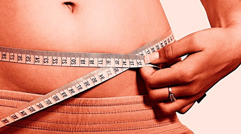 mujer midiendo su cintura con cinta metrica conoce la hormona que no te permite bajar de peso