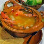 tostadas limones especies y plato de barro con pozole de camaron sobre una mesa