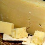 trozo grande de queso con trozos mas pequenos al frente el queso genera adiccion