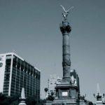 fotografia en blanco y negro del angel de la independencia junto a otros edificios en mexico