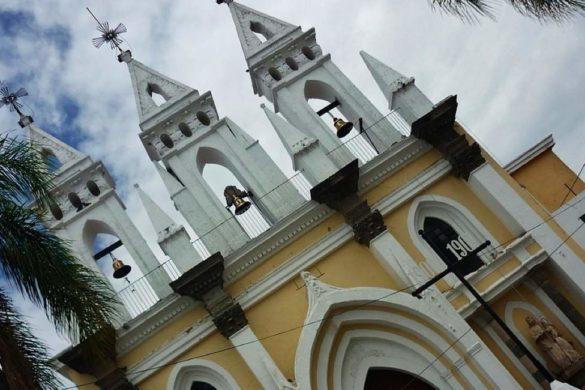 fotografia iglesia de tonala en color blanco y amarillo palmeras y al fondo nubes blancas