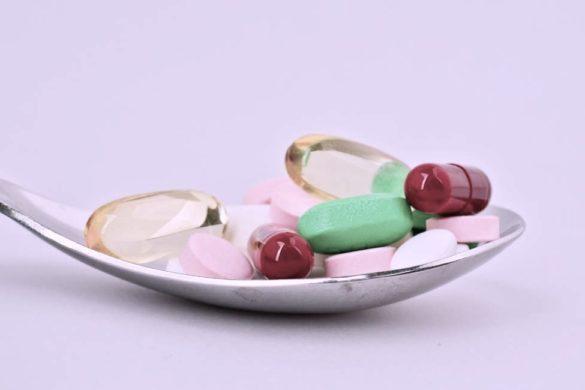 fondo blanco con cuchara llena de pastillas de diferentes colores y tamanos