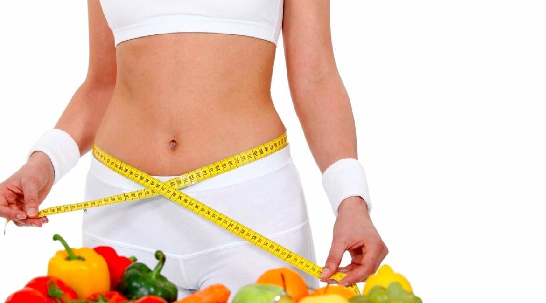 abdomen de mujer con cinta metrica y algunas frutas para darte consejos para bajar de peso