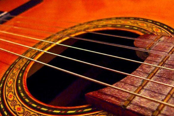 fotografia de guitarra acustica se notan las seis cuerdas y algunos trastes