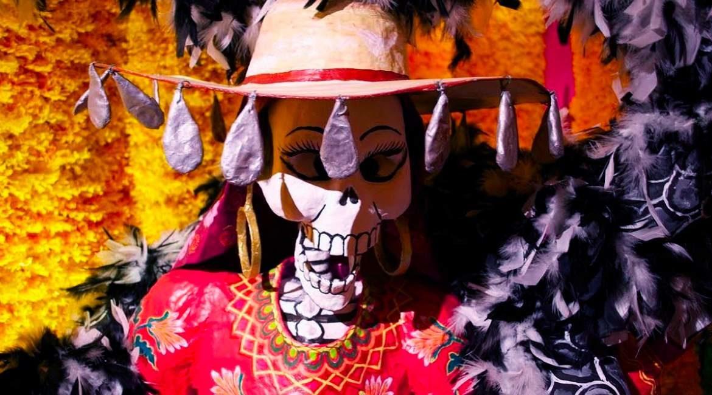 catrina con sombrero plumas y cempasuchil simbolizando el dia de los muertos prehispanico