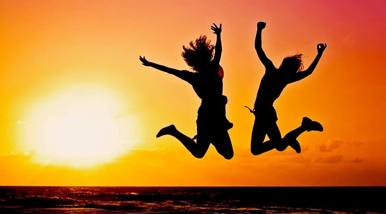 puesta de sol y dos personas saltando estas son las cosas que las personas sanas hacen