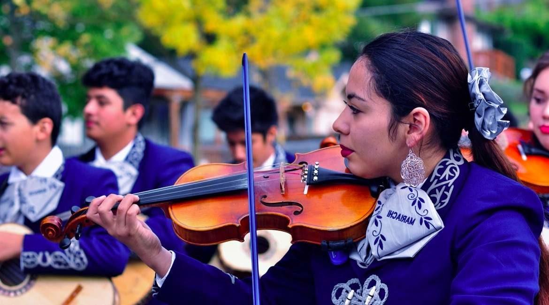 mujer marichi tocando el violin al fondo otros tres integrates del marichi conoce su origen