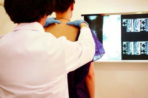 doctora con bata blanca masajeando cuello y espalda de un joven al fondo unas radiografias