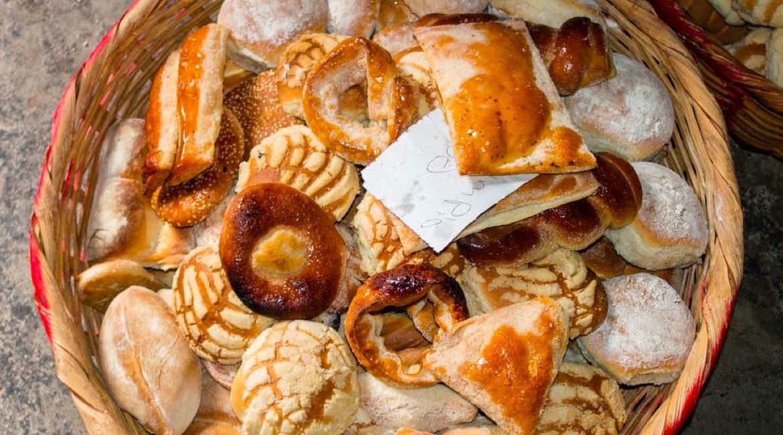 canasta grande para pan hecha de mimbre con diferentes piezas de pan dulce