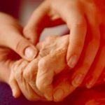 manos jovenes dando masaje a manos de un adulto mayor rutina para disminuir el parkinson